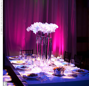 Floating candles, white floral spheres, calla lilies, and wheat grass arranged at different levels set a dramatic scene.