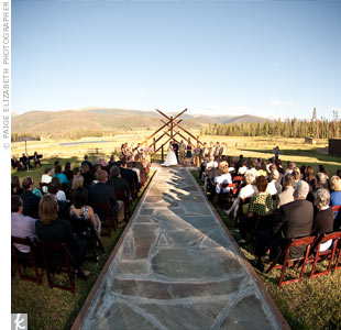 Guests sat on either side of a river stone aisle as CaraMae and Matthew exchanged vows under a frame of Aspen logs at Devil's Thumb Ranch.