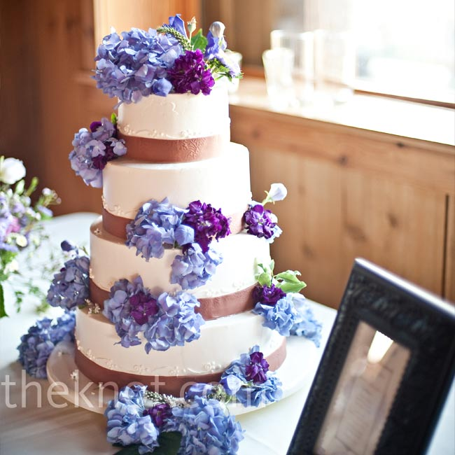 Purple flowers cascaded down the tiers of the white buttercream cake. Chocolate-colored ribbon pulled the color scheme together.