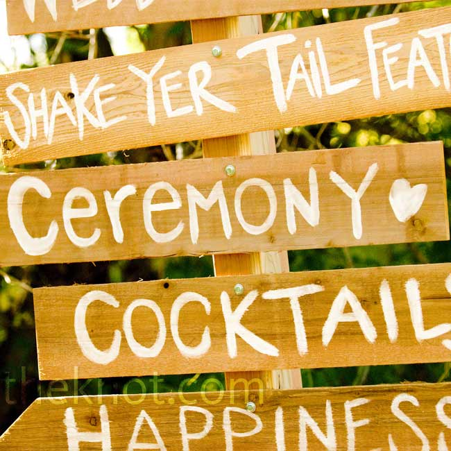 "A large wooden sign with painted words like ""happiness"" and ""ceremony"" directed guests to Elizabeth's and Josh's DIY wedding."