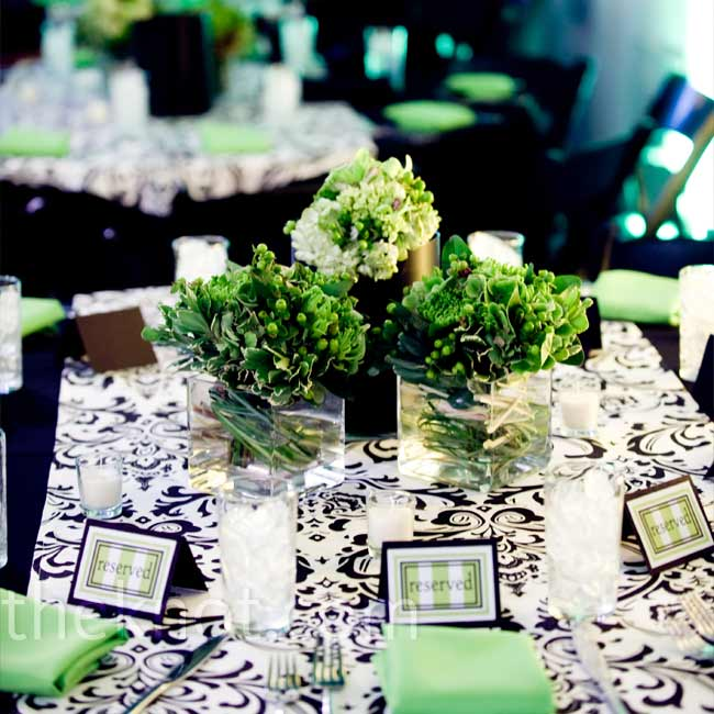 Yellow and green up-lighting gave the white walls of the reception space a fresh glow. Small square vases of green hydrangeas, spider mums, and hypericum berries popped against the black-and-white damask tablecloths.