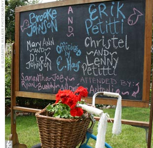 Instead of programs, Brooke and Erik put all the info guests needed for the ceremony on a chalkboard. The basket of a vintage, bright-blue bike was the perfect vessel for the red geraniums.