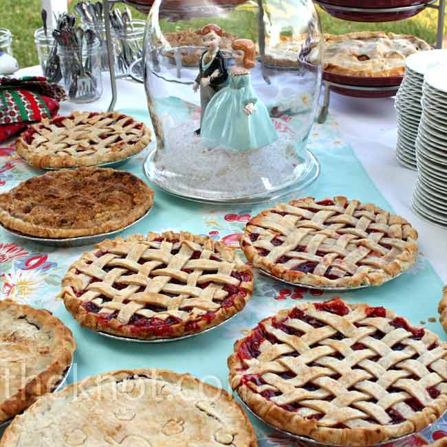 Brooke and Erik decided that pies felt more fun and summery than cake, so they ordered 44 fresh pies like cherry, apple, peach, and blueberry and displayed them all on a large table with a vintage tablecloth. As a centerpiece, they placed a vintage porcelain bride and groom inside a glass cloche.