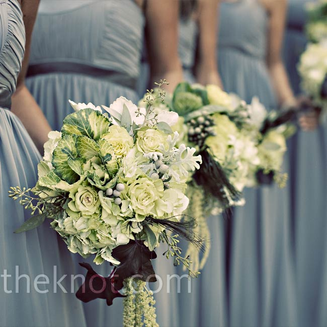 The bridesmaids carried green and white bouquets of roses, kale, hydrangeas, dusty miller, silver brunia, seeded eucalyptus, begonia leaves, and a few peacock feathers wrapped in gray satin ribbon to match their dresses.