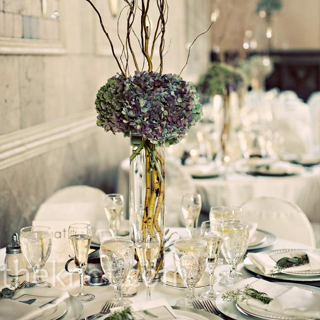 The couple's florist alternated between two centerpieces—the tables that lined the walls of the room had 18-inch, glass cylinder vases filled with tall willow branches (complete with hanging crystals) and antiqued hydrangeas.