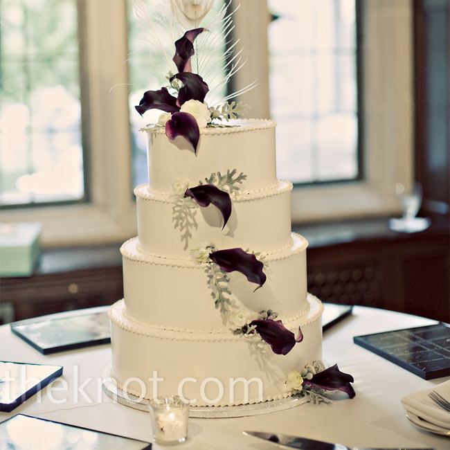 Black calla lilies, ivory ranunculus and dusty miller cascaded down Christine and Zac's all-white buttercream wedding cake to give it color while a tall, bleached peacock feather topped off the look.