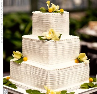 Joanna and Hebert served a three-tiered, buttercream-frosted wedding cake at their evening reception. The square tiers evoked a city feel while green cymbidium orchids, salal leaves, and yellow craspedia added a rustic touch.