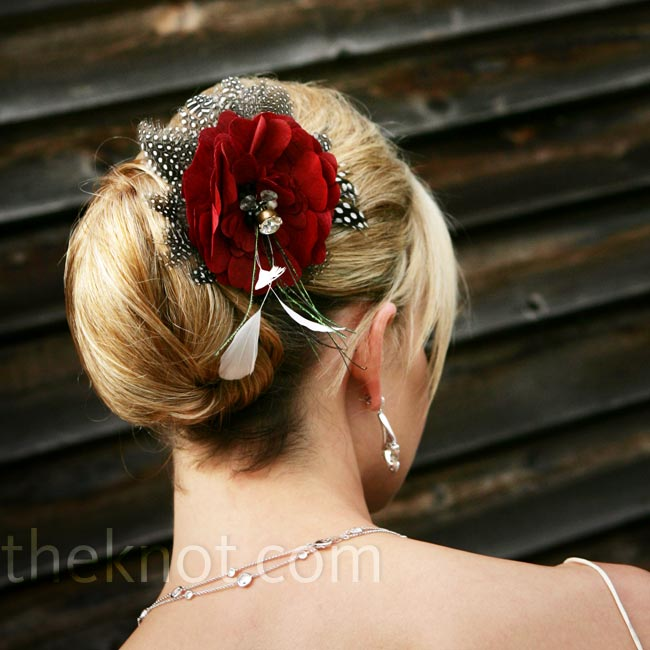 A hairpiece made with black and white feathers and a red silk flower embellished the bride's fluid chignon updo.