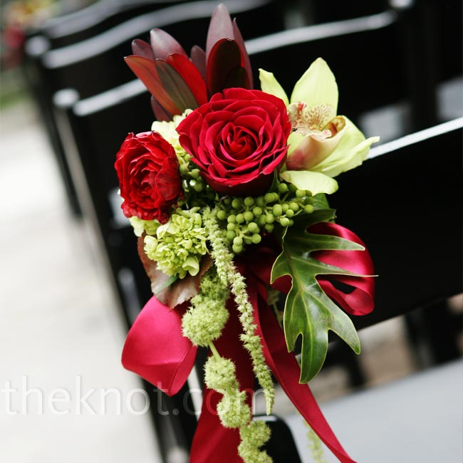 Alison didn't want to block the fountain or surrounding greenery in Bear's Garden, where the couple wed, so her florist dressed up what was already there with little bunches of red and green flowers tied to the aisle chair backs with red ribbon.