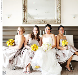 Yellow pom pom balls, cymbidium orchids, calla lilies, and hydrangea stood out against the bridesmaids' silver-grey dresses.