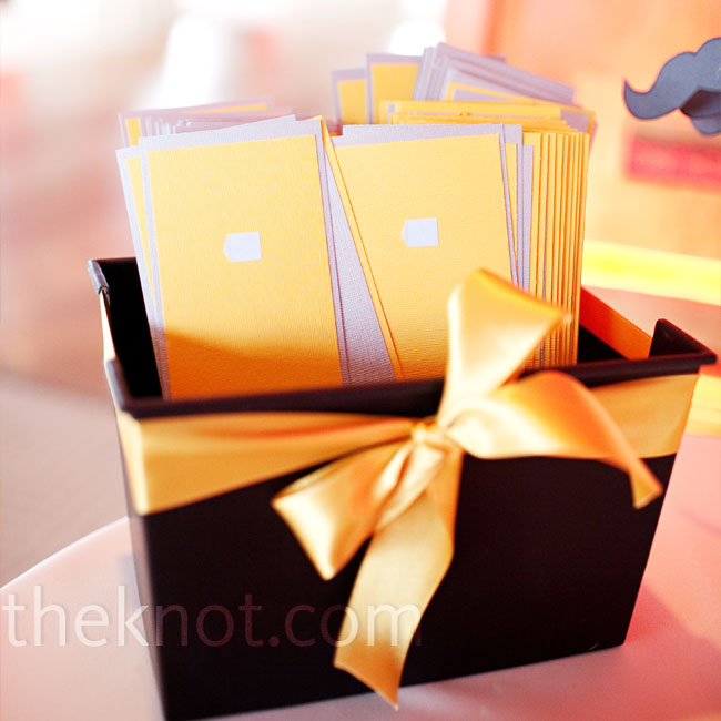 Ana made the ceremony programs with supplies purchased from a craft store. They printed the programs on yellow linen paper, bound them in gray cardstock, and tied them with yellow satin ribbon.