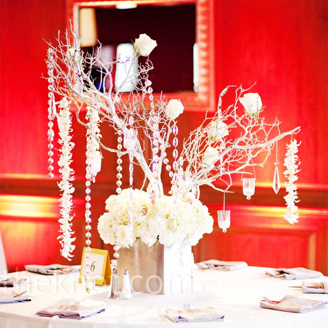 The bride and groom decided to have three different types of centerpieces at the reception. Some tables were decorated with an arrangement featuring silver spray-painted Manzanita branches decked out with crystals, orchid strands, roses, and candles.