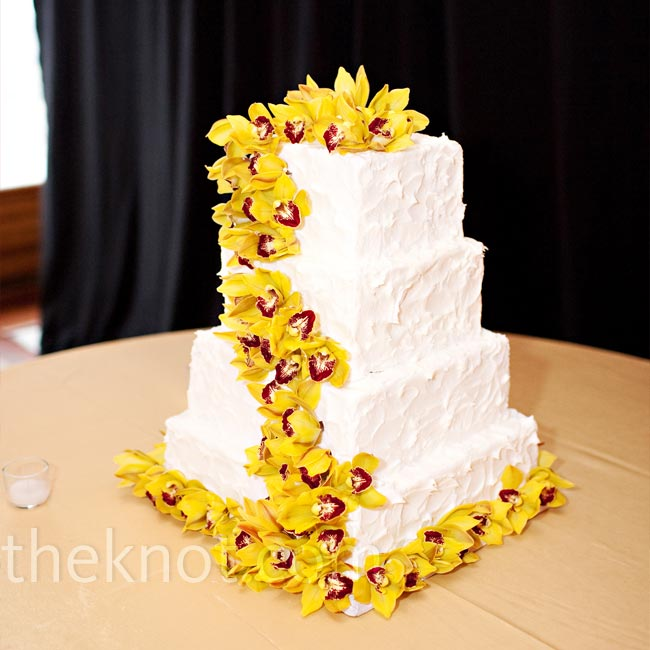 Real orchids cascaded down the side of the bride's four-tier buttercream cake. For added texture Ana had the baker decorate each layer with rings.