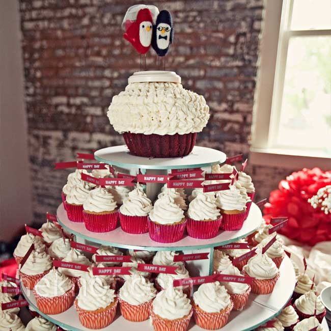 "Instead of a cake, Kim and Zak wanted guests to enjoy cupcakes. Each tier featured a different flavor. A mix of patterns on the cupcake cups and the little ""happy day"" flags that Kim made herself upped the fun factor."