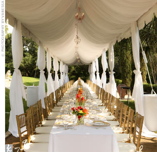 The dinner took place under a tent, which was dramatically dressed with chandeliers and flowing curtains. Instead of several small tables, one long banquet table was set with Melissa and Stuart at the head -- literally everyone was sitting at the bride and groom's table!