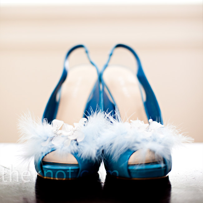 "Ryan changed from her champagne color peep toe sling backs into more sassy blue shoes for the reception. She dressed them up with shoe clips she made herself. ""I took some ice blue feathers, some crystals and beads, wired it all together and voila,"" she exclaims!"