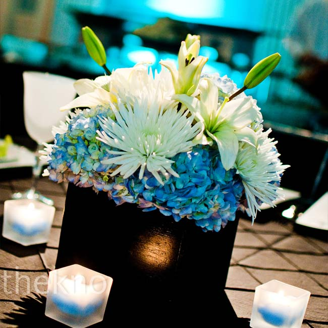 The tables in the ballroom were decorated with three different centerpieces: a tall centerpiece that featured an arrangement of hydrangea mixed with black branches illuminated from the bottom by an LED candle, a low centerpiece of blue and white hydrangea nestled in a black box and non-floral centerpiece featuring a lamp with a black and white dama ...