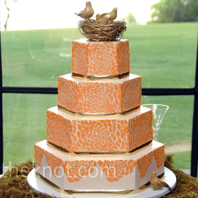 Shelly's cake was displayed on a bed of fresh moss. Each octagonal tier was decorated with a peach floral applique and separated by a gold band. The cake was topped with a decorative gold bird's nest.
