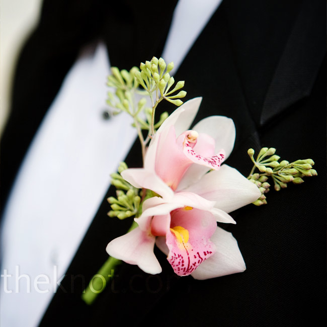 """I wanted to save the boys from all the pink, so only the groom wore a light pink boutonnière,"" explains Kelly. The groomsmen sported white orchids."