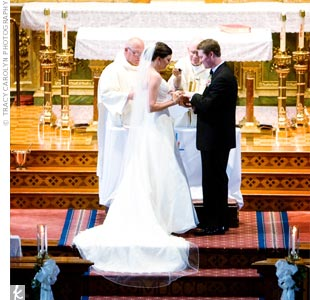 "Kelly and Joe married in a traditional Catholic ceremony at the Shrine of St. Joseph. The bride liked that it had the ""feeling of a European church."" The church is really ornate so the couple limited decorations to candles and white bows along the aisle."