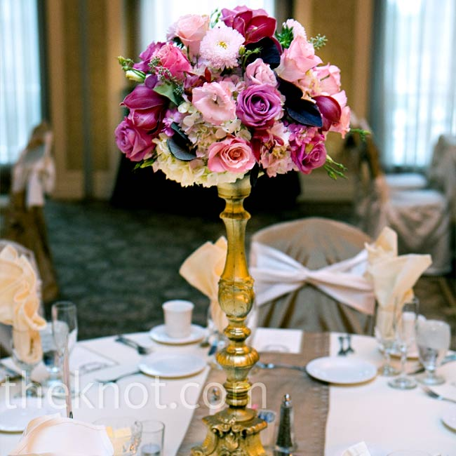 Kelly and Joe added a textural element to their reception space by varying the heights of their centerpieces. Half of the tables featured tall arrangements in varying shades of pink—including hydrangeas, stock, lisianthus, roses, asters, orchids, and protea -- which sat atop tall gold stands. The other half were lush, low centerpieces arranged in g ...