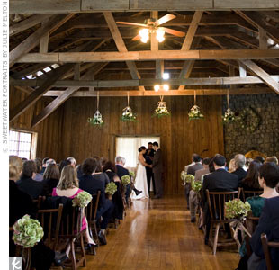 The ceremony took place in a small room, attached to the larger reception hall, with rustic wooden chairs and an exposed, wood-beam ceiling. Bouquets of green and ivory hydrangeas decorated the aisle and hanging bouquets marked the altar.
