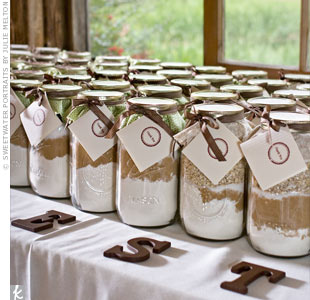 "The creative couple made their own favors: mason jars filled with ingredients for baking cookies -- guests could choose between chocolate chip and oatmeal raisin. They bought the jars online and filled them with the baking goods they bought at Sam's Club. Then, they decorated them with ribbon and recipe cards stamped with a ""thank-you."""