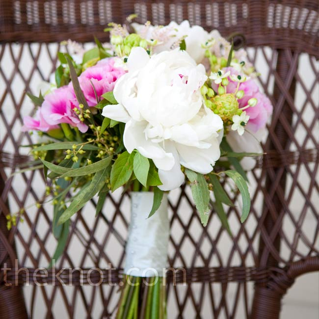 A loose bouquet of ivory peonies, green coxcomb, white stars of Bethlehem, tuberose, pale pink astilbe, seeded eucalyptus, blueberry foliage, gedetia, and green fiddleheads worked well for the couple's garden ceremony.