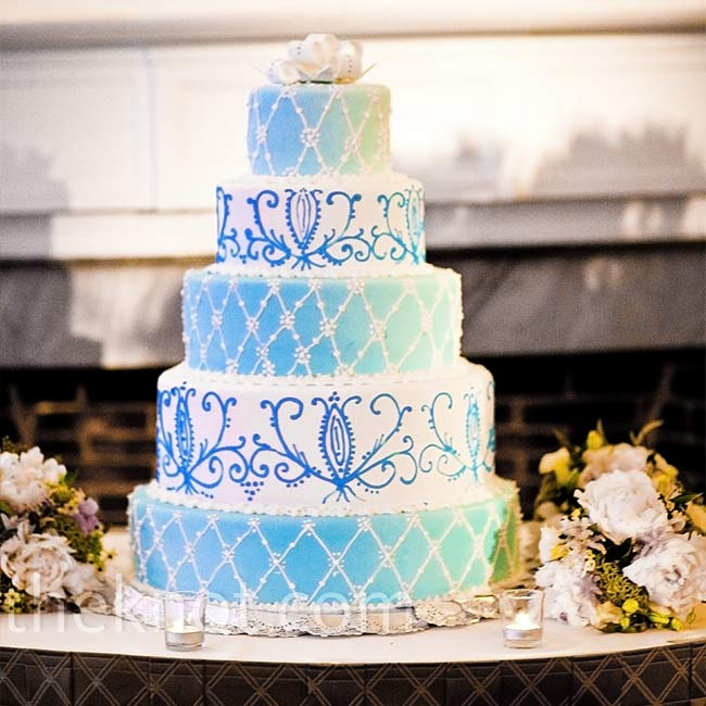 "Lindsay and Michael's five-tiered cake was decorated with white and ""Bedford"" blue buttercream frosting and piping. For the topper: a white fondant bow."