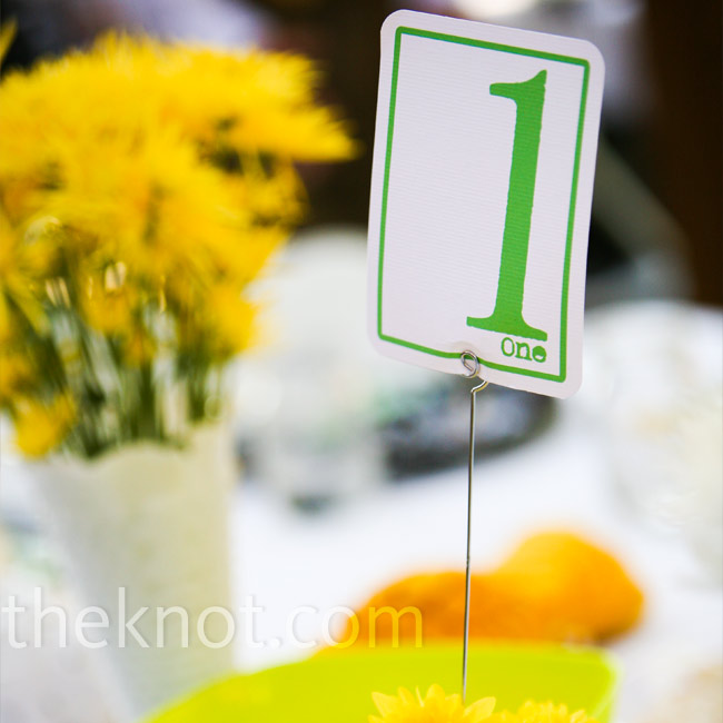 "Andrea loves bright, ""happy"" colors, and yellow has always been one of her favorites, so she knew she wanted it incorporated into the wedding. The couple put a fun twist on black and white by adding yellow and green to the mix."