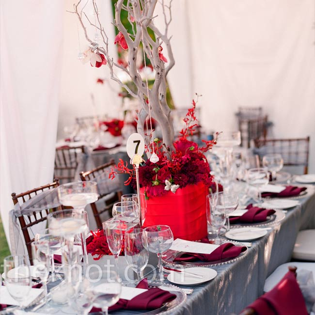 Elegant centerpieces of red flowers, crystals, and feathers, arranged in silver or red boxes, decorated the tables. Silver branches styled with hanging crystals were added to some for extra height.