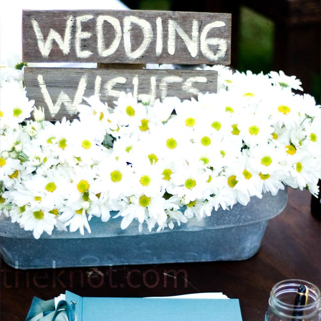"Matching the centerpieces, an arrangement of white daisies in galvanized buckets decorated the guest book table. A wooded sign painted with ""wedding wishes"" let guests know what to do."