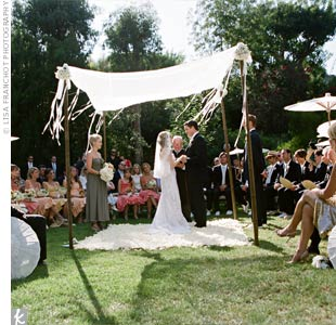 Guests sat or stood in a circle around Courtney and Andrew for a more intimate feel. The couple stood on a blanket of white rose petals, beneath four bamboo poles draped with white fabric.