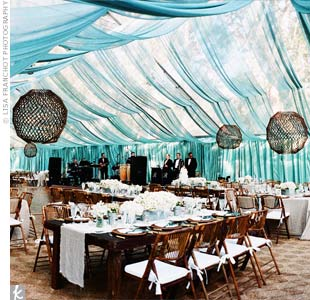Dinner was served beneath a clear tent with transparent teal fabric draped from the ceiling, allowing guests to see the twinkling lights on the trees above. For a twist on chandeliers, wooden sticks were shaped into balls and hung overhead, with candles inside.