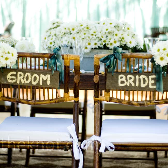 Courtney and Andrew sat in chairs marked specially for them with painted wooden signs and white daisies.