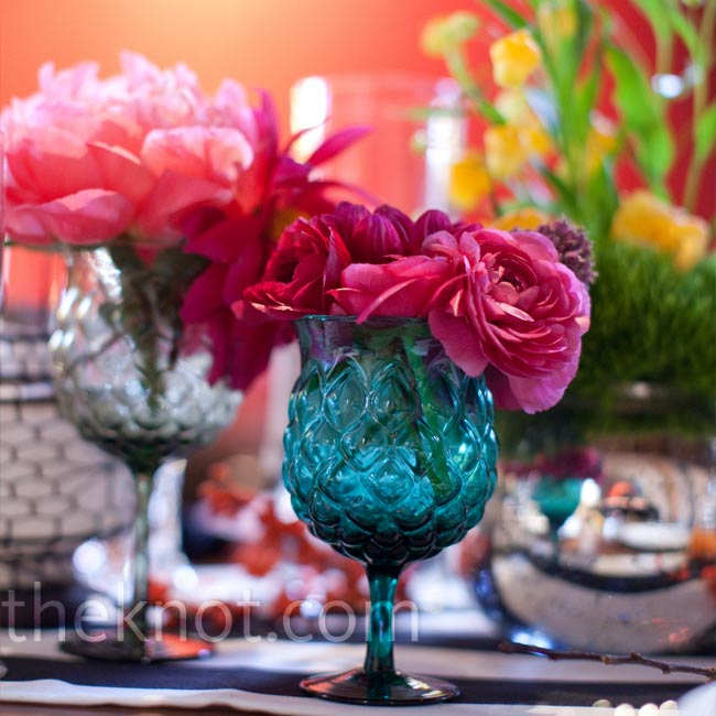In addition to the pumpkins placed along the table runners, the florist set bright-pink and yellow blooms in various colored glasses and containers.