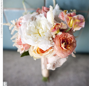The bridesmaids carried a mix of peach, coral, and pale pink roses and ranunculus with white accents.