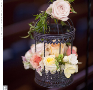 To bring Min and Jason's style to the already beautiful ceremony location, birdcages were filled with pale-pink and peach roses and hung from shepherd's hooks along the aisle.