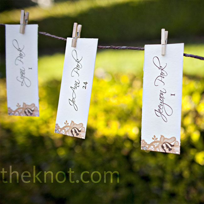 Small, ivory escort cards, printed with the same floral design as the invitations, hung from twine and mini-clothespins in Greystone Mansion's courtyard. Min placed them far away from the appetizers so guests would have to walk around the estate and mingle.