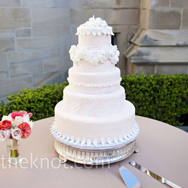 Min and Jason opted for a simple cake covered in a pale, peachy-pink fondant and decorated with ivory sugar flowers, feathers, and leaves for a whimsical look.