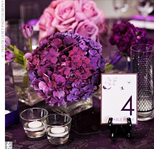 Like they did for most of the wedding décor, Theresa and Ken chose flowers in different shades of purple for the centerpieces, including tulips, hydrangeas, and roses. They were arranged in glass vases of varying shapes and textures.