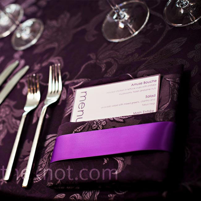 The couple chose a bright-purple ribbon to wrap around the eggplant napkins.