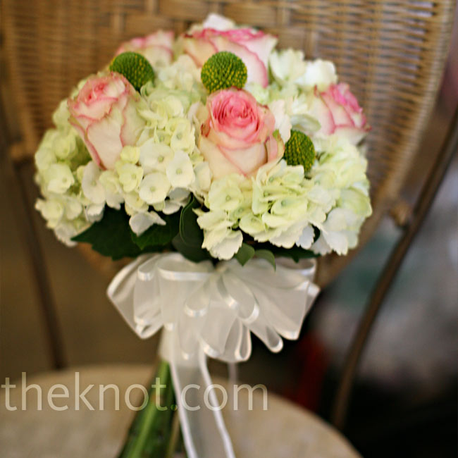 The bride carried a round bouquet of green and white hydrangeas, roses, and craspedia. A sheer white ribbon, trimmed in satin, tied the stems together.