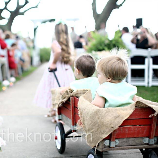 The flower girls pulled the couple's nephews in a Radio Flyer wagon draped in burlap and sea shells. The tots sported light green rompers with their initials embroidered on the front.
