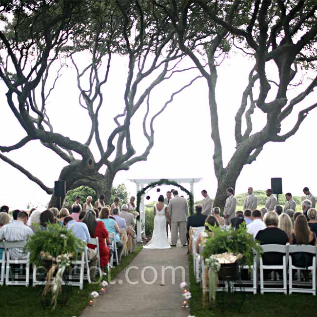 Deanne and Will stood under a white arbor laced with greenery, mums, and pink raffia, overlooking the ocean. A cluster of Century oaks shaded them from the sun.