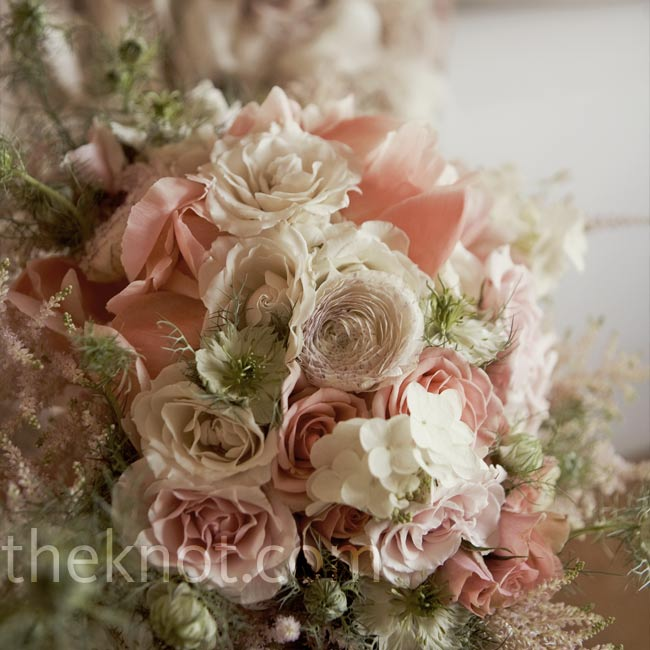 The pale pink bouquet of roses, hydrangeas, and wildflowers mirrored the soft shades in Ginny's capelet.