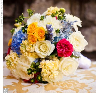 The bouquet represented each color from the wedding palette with blue hydrangeas, green hypericum berries, dusty miller, and yellow, fuchsia, and white roses and dahlias.