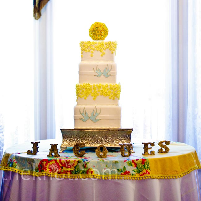 After a mishap with their first baker and only a week until the wedding, Celso's Cakes saved the day with a gorgeous four-tier confection, decorated with the couple's signature tattoo-print birds and yellow flowers.