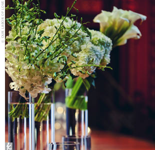 For a dramatic contrast against the shorter arrangements, single blooms of white jewel roses, amaryllis, and hydrangeas draped over vignettes of tall candlestick vases.