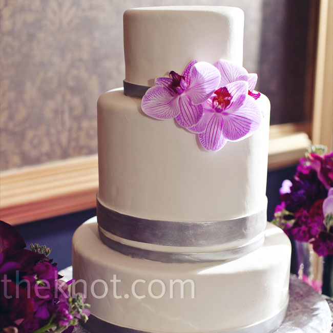 Fresh phalaenopsis orchids topped the sleek and simple white cake adorned with hand-painted silver bands.